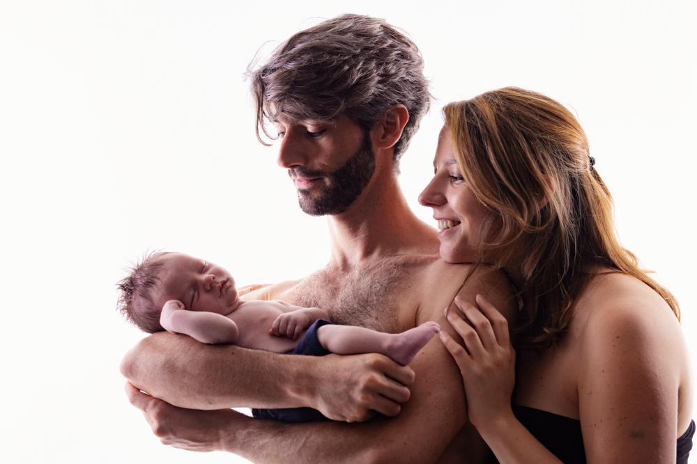 Photo de bébé nouveau né avec ses parents maman et papa en couleur en studio en high key éclairage façon aubade