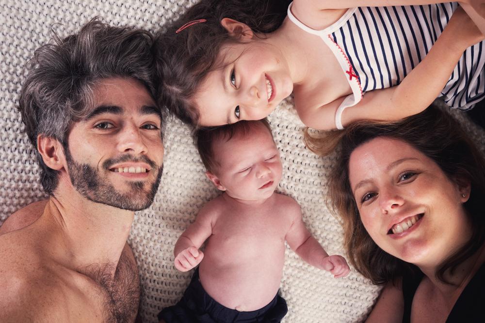 Photo de bébé nouveau né en famille avec papa maman et sa petite sœur en studio
