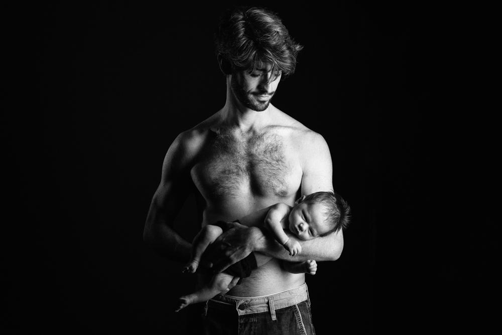 Photo de bébé nouveau né avec papa en noir et blanc en studio en low key